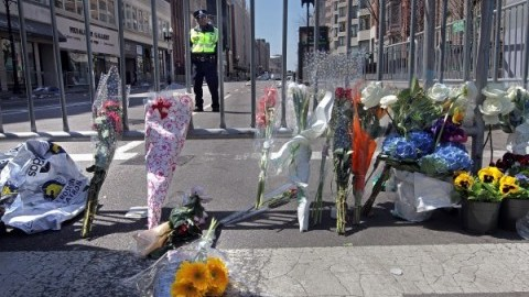 Flowers are left at a barricade at the intersection of Boylston Street and Arlington Street on Tuesday, April 16, 2013, in Boston, Massachusetts. The city is in mourning today for three killed and at least 144 wounded in a