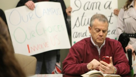 Eddie Hull uses his phone while students vote on whether to stay or go during a student protest on Feb. 24, 2012. (Collegian File Photo)