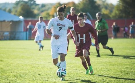 Jake Alvaro holds off a Harvard defender at Rudd Field on Friday (Judith Gibson-Okunieff/Daily Collegian)
