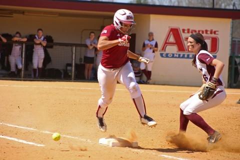 Quiana Diaz-Patterson jumps to avoid the ball as she runs to first base.  (Robert Rigo/Daily Collegian)