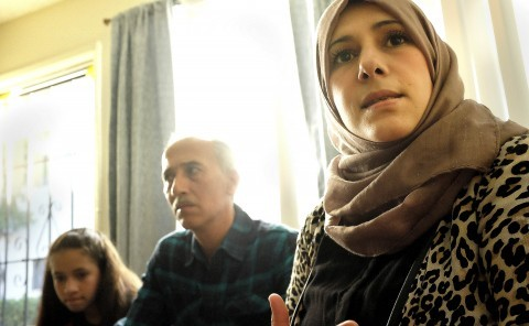 (Sahar Kassab, right, speaks to a reporter off camera next to her husband Basel Awarek, center, and daughter Laila Awarek, left. They are refugees from Homs, Syria.  John Gastaldo/San Diego Union-Tribune/TNS)